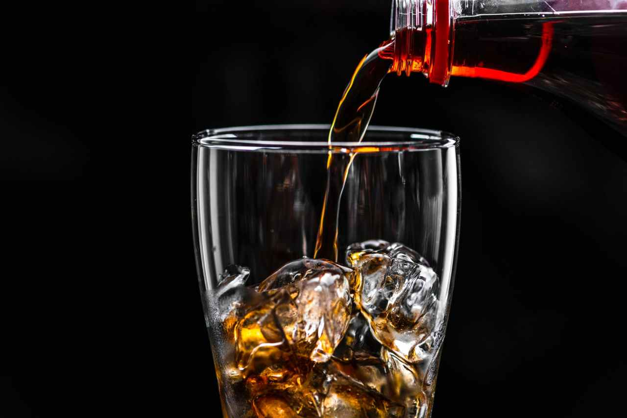 brown liquid pouring on ice drinking glass