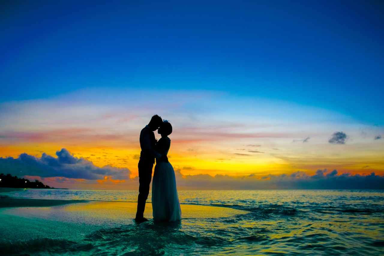 man and woman standing at seashore