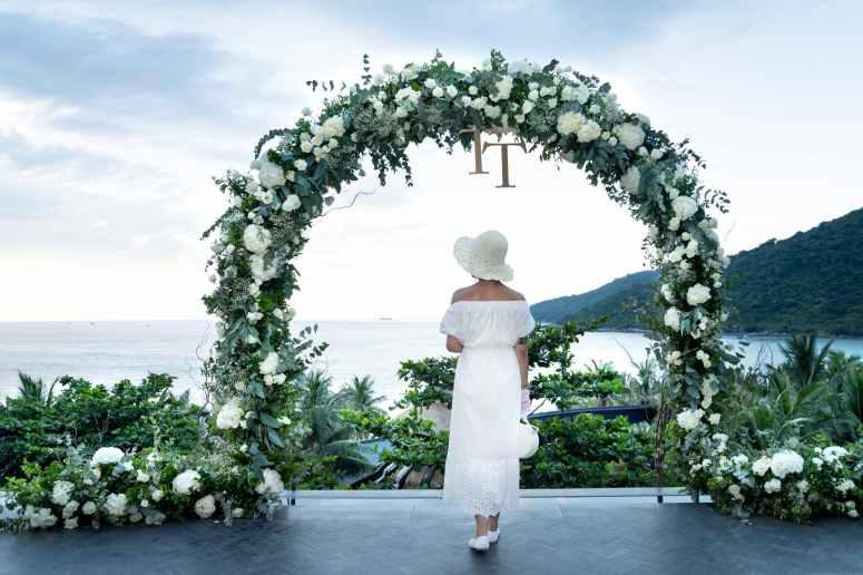 photo of woman wearing white dress near flower arbor